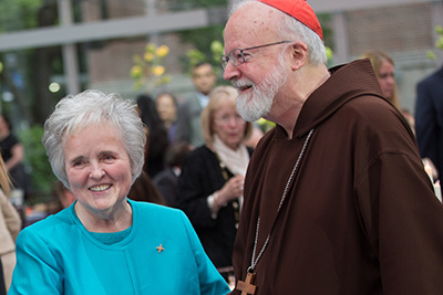 Sister Janet wearing a turquoise suit and smiling with Cardinal Sean O'Malley, who is wearing a brown robe, during the 40th anniversary Gala