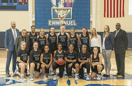 The women's basketball team in their black and blue uniformes posing with their coaches in the Emmanuel College gymnasium