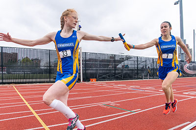 Two women track and field athletes in blue and gold track and field uniforms passing a blue and gold baton during a relay race