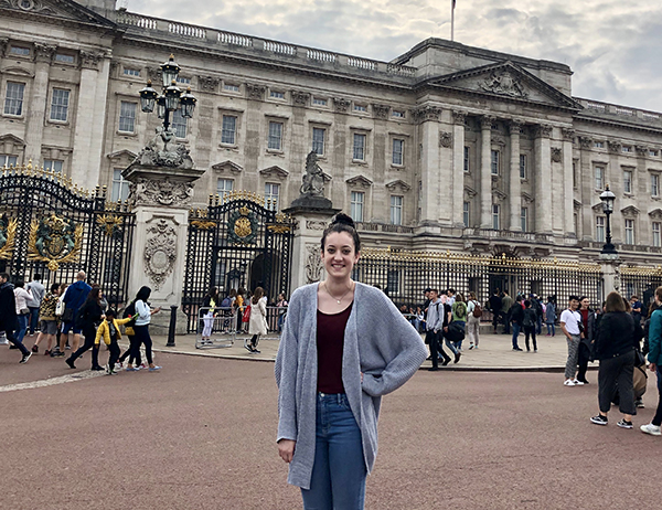 Female student stands outside Buckingham Palace in London