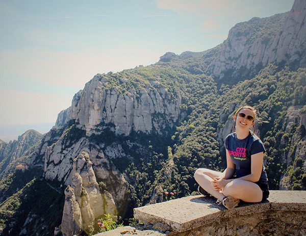 a female student sits on a wall overlooking the mountains in Barcelona
