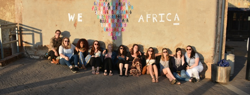 Students sitting in front of wall that says We Love Africa with colorful handprints