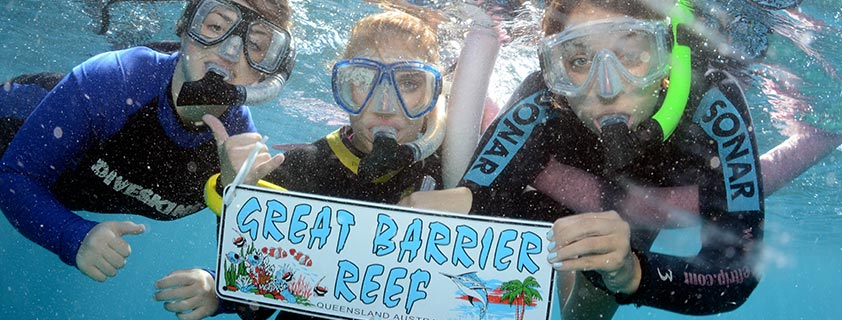 Three students snorkeling holding a sign that says Great Barrier Reef