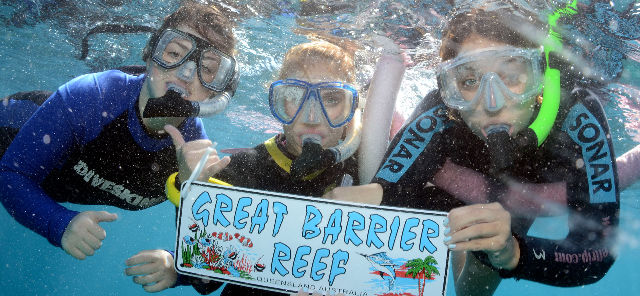 three female students snorkeling, holding a sign that says Great Barrier Reef