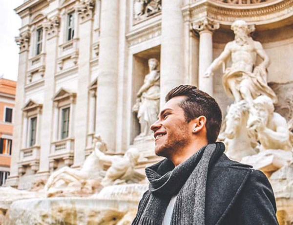 male student in front of the Trevi fountain in Rome, Italy